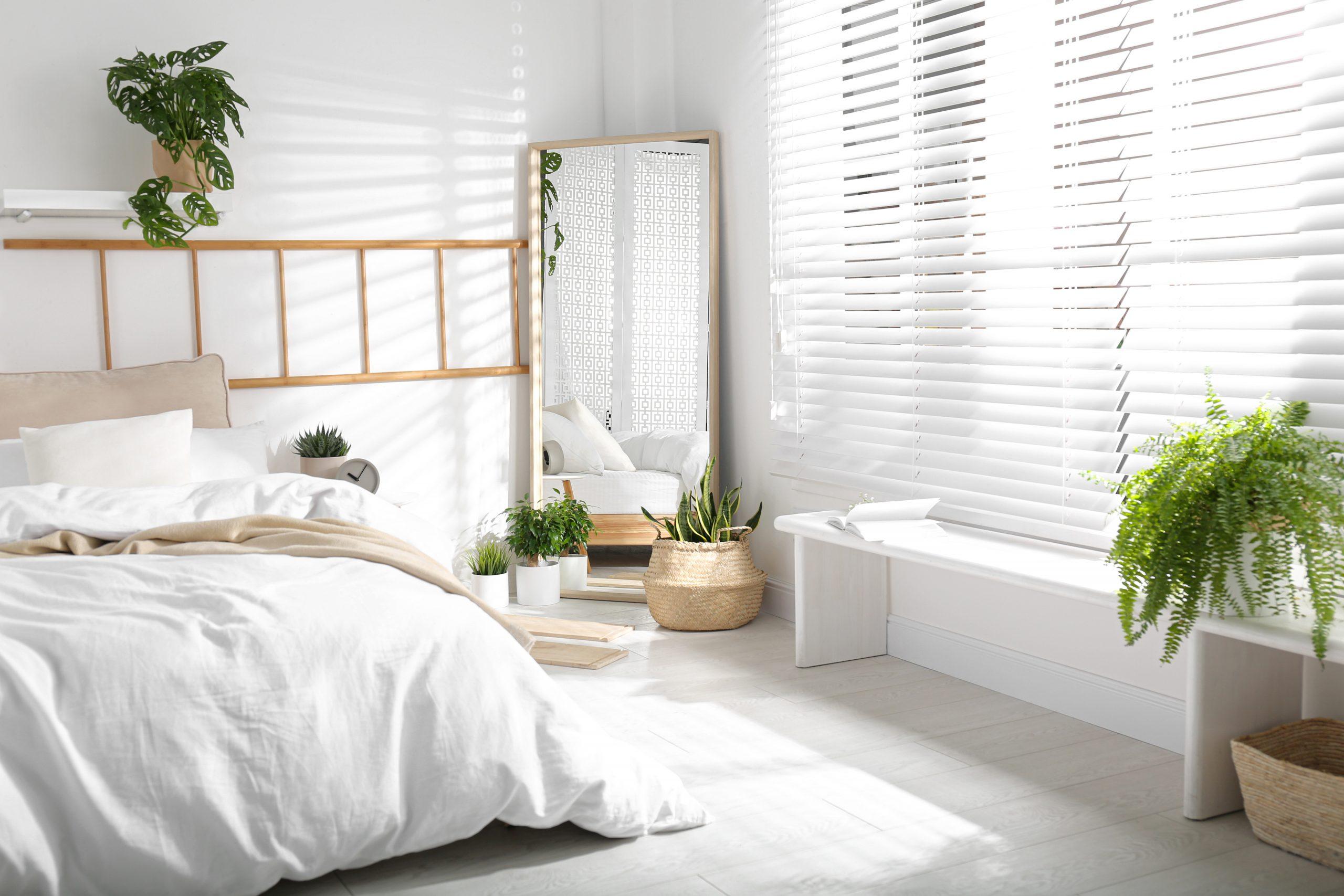 Moderna spalna so zrkadlom a bielymi zaluziami svetlo