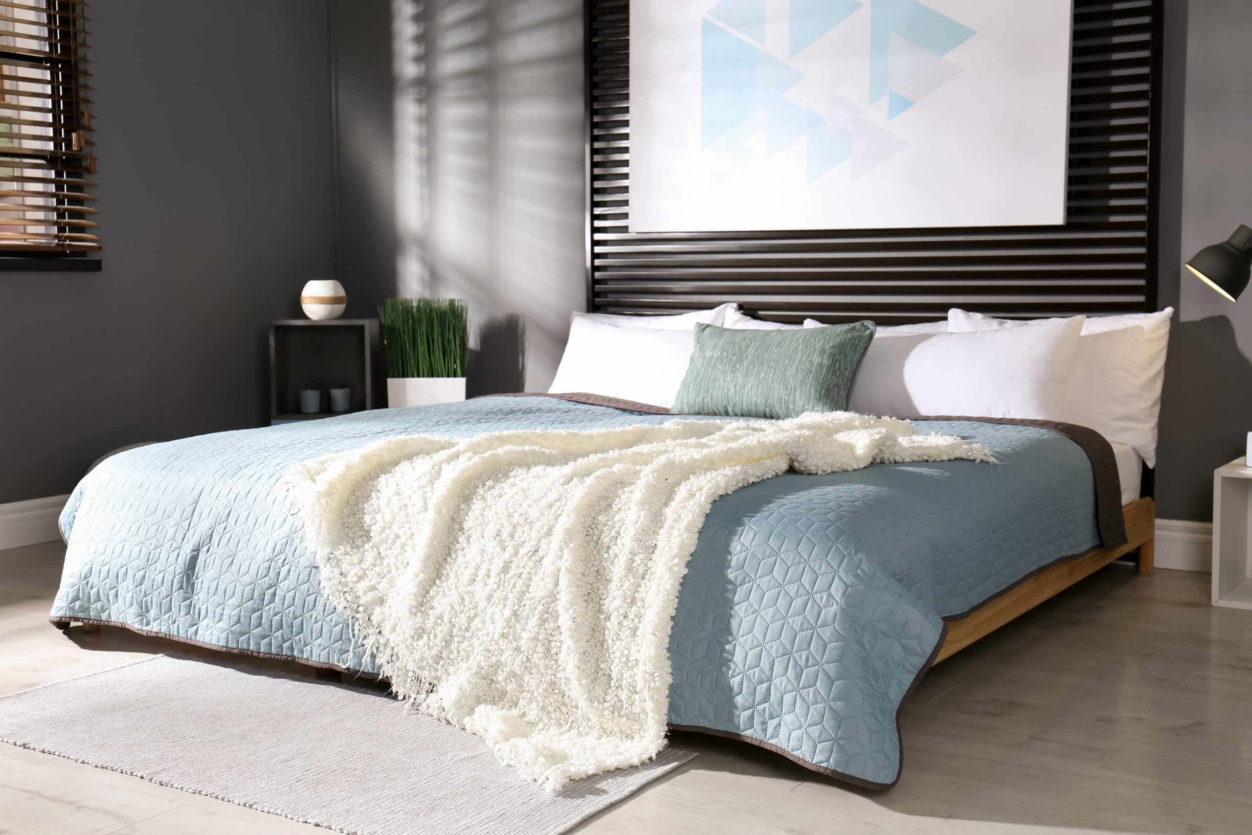 moderna pohodlna postel v spalni s tienenim drevenymi zaluziami